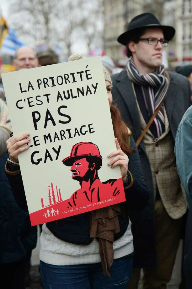 "A woman holds a placard reading ""priority is Aulnay, not gay marriage"" as she demonstrates against France's gay marriage law in an attempt to block legislation that will allow homosexual couples to marry and adopt children, on March 24, 2013 in Paris. Photo: ERIC FEFERBERG, Getty Images / 2013 AFP"