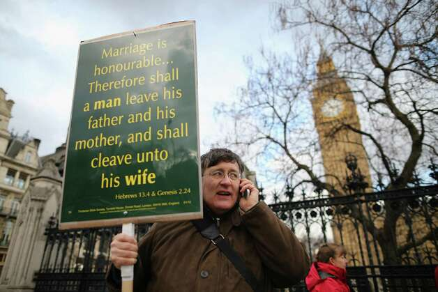 A protester stands in front of Parliament holding a placard with quotes from the Bible on February 5, 2013 in London, England. Photo: Dan Kitwood, Getty Images / 2013 Getty Images
