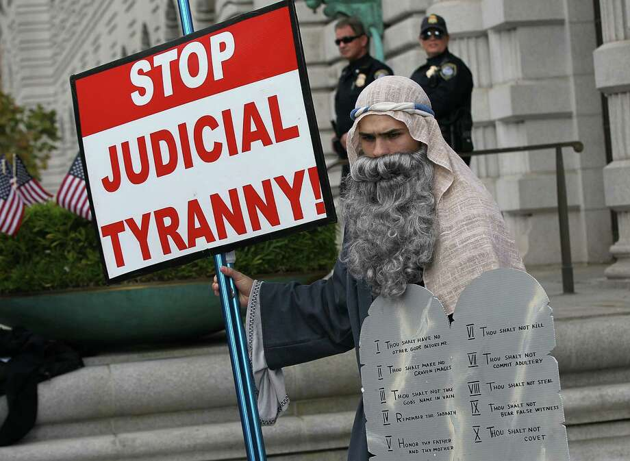 A supporter of Prop 8 is dressed as Moses as he holds a sign during a demonstration outside of the Ninth Circuit Court of Appeals. Photo: Justin Sullivan, Getty Images / 2010 Getty Images