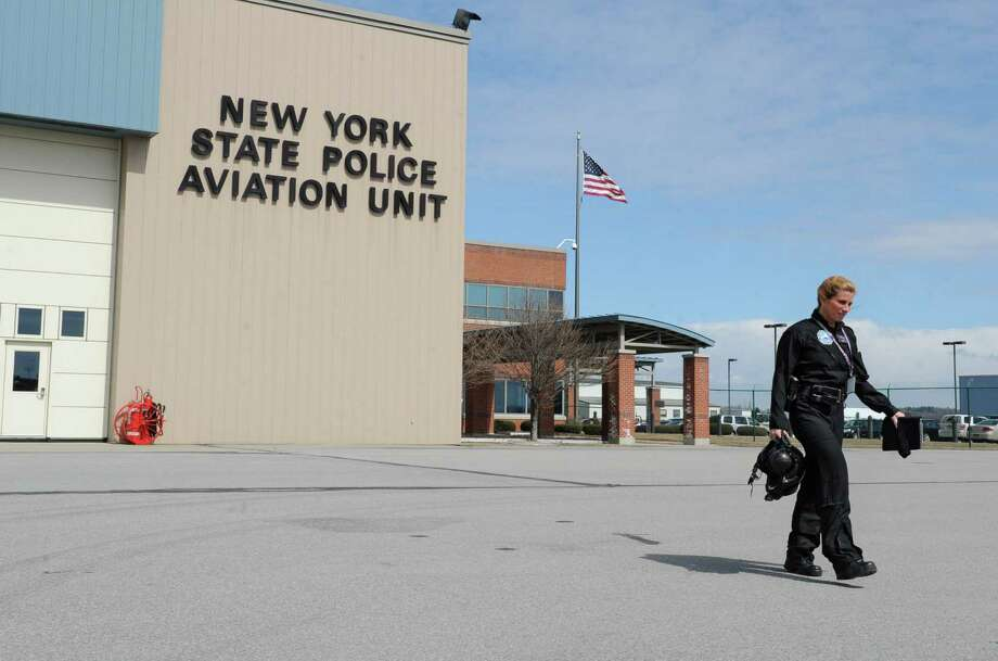 Kathy Humphries, Tech Sgt. with the NYS police, walks out of the State Police aviation hanger to a helicopter on Wednesday, March 27, 2013 in Colonie, N.Y.  Tech Sgt. Humphries recently made New York State Police history when she piloted an all female medevac flight mission. On that mission were two female paramedics from Colonie, Mary Beth Pulver and Mary Pat Provost. Humphries is the first and only NYS Police helicopter pilot. The former U.S. army pilot has been with the state police for 18 years.(Lori Van Buren / Times Union) Photo: Lori Van Buren