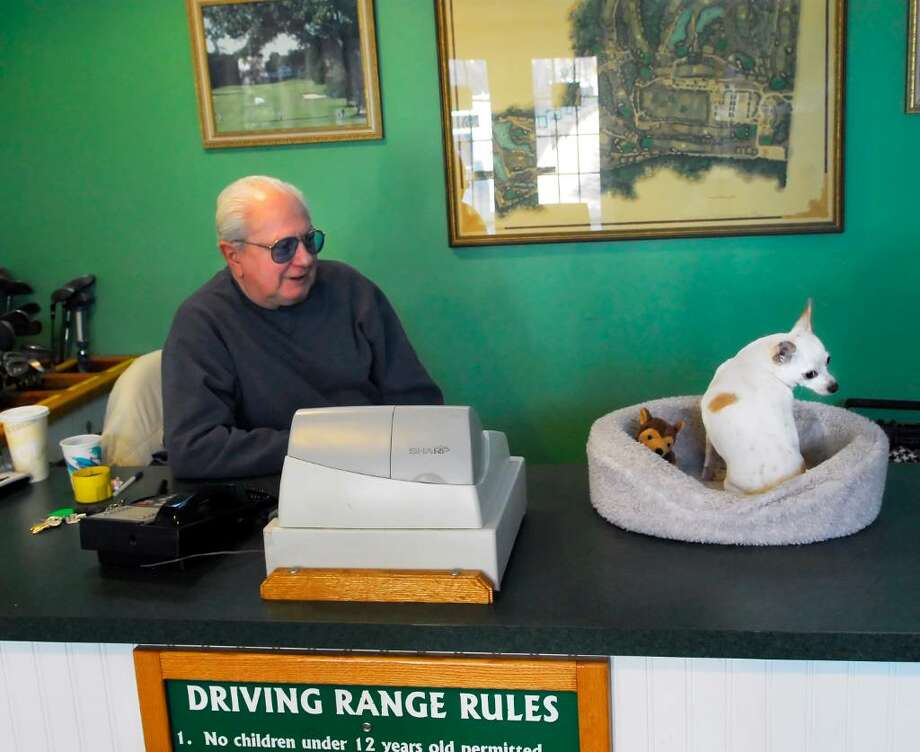 "Ed Koda, 84, supervisor of the driving range at Sterling Farms Golf Course in Stamford, passes the day waiting for customers with his 6-year-old Chihuahua sidekick, Cha-Cha, Tuesday, Dec. 5th, 2009.  Koda said he has worked at the course for over a decade and that the Chihuahua is his favorite breed.  Koda also said legendary golfer and friend Lee Trevino gave a Chihuahua to him that was flown up from Mexico and that the dog was so difficult and barked so much that he gave it to his mother and was amazed to see his mother and the difficult Chihuahua become buddies, ""my mom was the only person that dog trusted"". Photo: Bob Luckey / Stamford Advocate"