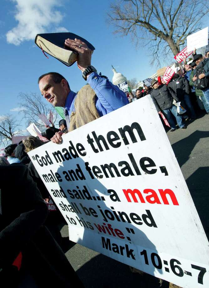 An anti-gay marriage activist holds up a Bible and placard as he marches in front of the Supreme Court. Photo: KAREN BLEIER, Getty Images / 2013 AFP