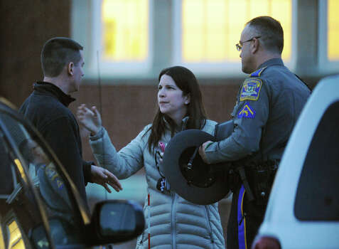People are escorted to their car by a state trooper after the state police debriefing for families involved in the Sandy Hook shooting at the Newtown Municipal Center in Newtown, Conn. on Wednesday, March 27, 2013. Photo: Tyler Sizemore / The News-Times