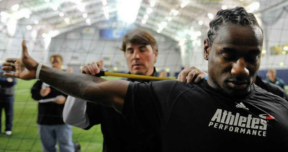 UConn linebacker Sio Moore right, has his arm measured by Panthers scout Robert Haines during UConn's NFL football pro day in Storrs, Conn., Wednesday, March 27, 2013. (AP Photo/Jessica Hill) Photo: Jessica Hill, Associated Press / FR125654 AP