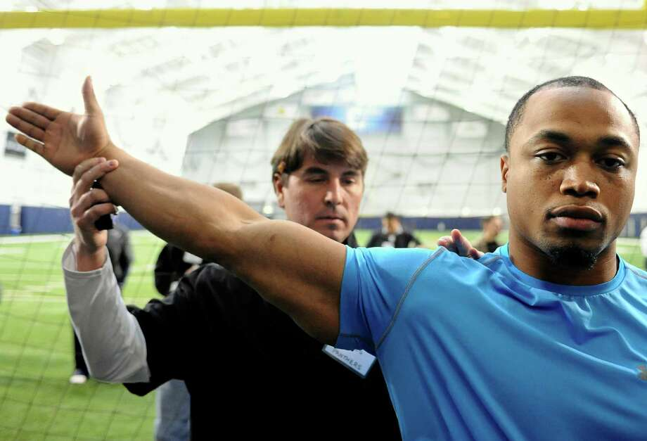 Defensive end Trevardo Williams, right, is measured by Carolina Panthers scout Robert Haines during UConn's NFL football pro day in Storrs, Conn., Wednesday, March 27, 2013.  (AP Photo/Jessica Hill) Photo: Jessica Hill, Associated Press / FR125654 AP