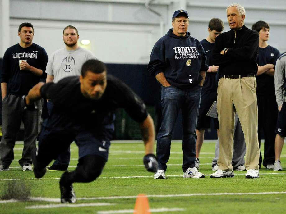 New England Patriots coach Bill Belichick, second from front right, and Connecticut football coach Paul Pasqualoni, front right, watch cornerback Dwayne Gratz, foreground left, workout for NFL football scouts during pro day in Storrs, Conn., Wednesday, March 27, 2013. (AP Photo/Jessica Hill) Photo: Jessica Hill, Associated Press / FR125654 AP