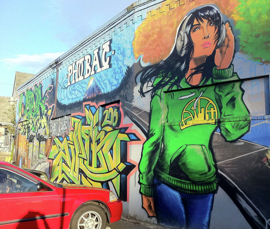 1. Can't go wrong with a beautiful woman rocking an emerald-green, old-school Sonics hoodie. This mural enlivens the wall of Pho Bac on Rainier Avenue South. (seattlepi.com photo).