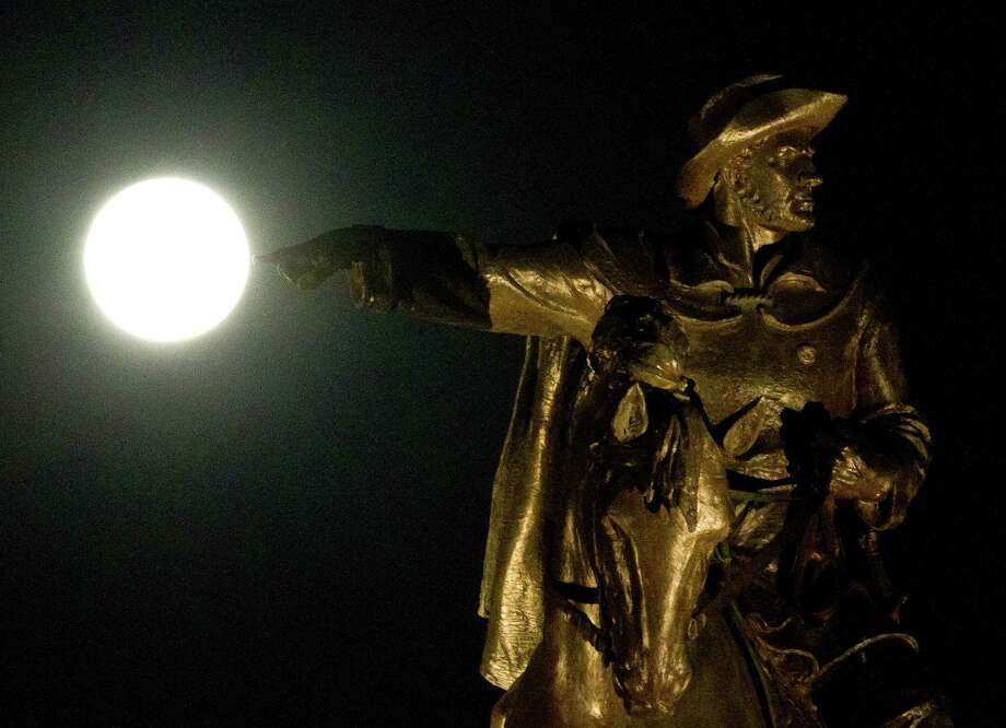 A full moon starts to set behind a statue of Sam Houston, Wednesday, March 27, 2013, at Hermann Park in Houston. (Nick de la Torre / Houston Chronicle) Photo: Nick De La Torre, Chronicle / © 2013 Houston Chronicle