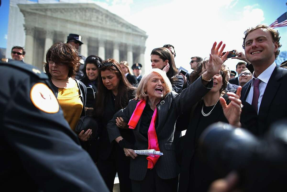 WASHINGTON, DC - MARCH 27: Edith Windsor (C), 83, is mobbed by journalists and supporters as she leaves the Supreme Court March 27, 2013 in Washington, DC. The Supreme Court heard oral arguments in the case 'Edith Schlain Windsor, in Her Capacity as Executor of the Estate of Thea Clara Spyer, Petitioner v. United States,' which challenges the constitutionality of the Defense of Marriage Act (DOMA), the second case about same-sex marriage this week. (Photo by Chip Somodevilla/Getty Images) *** BESTPIX ***