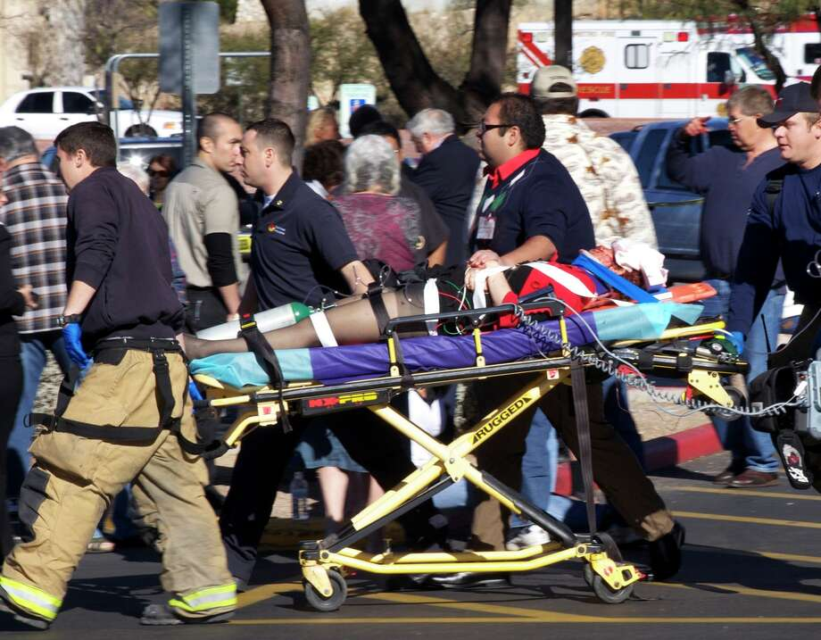 FILE - In this Jan. 8, 2011 file photo, Emergency personnel and Daniel Hernandez, an intern for U.S. Rep. Gabrielle Giffords, second right, move Giffords after she was shot in the head outside a shopping center in Tucson, Ariz. Hundreds of pages of police reports in the investigation of the shooting rampage were released Wednesday, March 27, 2013 marking the public's first glimpse into documents that authorities have kept private since the attack more than two years ago. (AP Photo/James Palka, File) Photo: James Palka