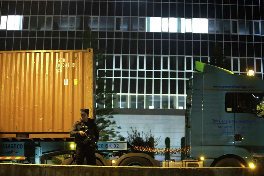 An armed police officer outside a bank in Nicosia, Cyprus, guards a truck reportedly carrying cash flown in from Frankfurt, Germany. Photo: Petros Karadjias / Associated Press