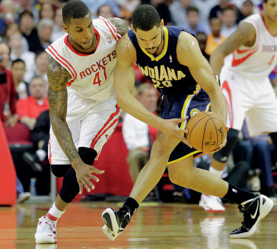 Rockets power forward Thomas Robinson, left, and Pacers power forward Jeff Pendergraph, right, chase the ball during the second quarter. Photo: James Nielsen, Houston Chronicle / © 2013 Houston Chronicle