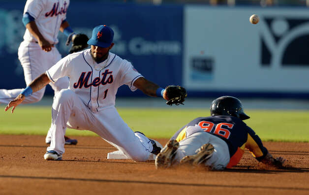 Carlos Correa, right, steals second as the throw gets away from Mets second baseman Jordany Valdespin during the first inning. Photo: Jeff Roberson, Associated Press / AP