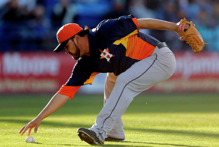Astros starting pitcher Edgar Gonzalez picks up a slow roller hit by Kirk Nieuwenhuis during the second inning. Photo: Jeff Roberson, Associated Press / AP