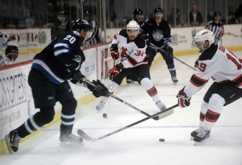 Albany Devils Phil DeSimone, center, and Mike Sislo, right, battle St. John's Richard Petiot during their hockey game at the Times Union Center on Wednesday March 27, 2013 in Albany, N.Y. (Michael P. Farrell/Times Union) Photo: Michael P. Farrell