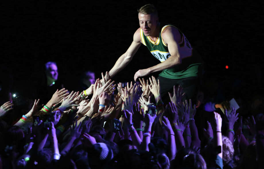 Surprise guest Macklemore, aka Ben Haggerty, greets screaming fans during We Day on Wednesday, March 27, 2013 at KeyArena in Seattle. The event brought thousands of middle and high school students together to hear from a list of celebrities and motivational speakers. This was Macklemore and Ryan Lewis' first public performance in their hometown since they kicked off their world tour with a show at WaMu Theater last year. We Day is a youth educational and empowerment event organized by the Free the Children charity. Students earned a seat at the event through their commitment to do good. Photo: JOSHUA TRUJILLO / SEATTLEPI.COM