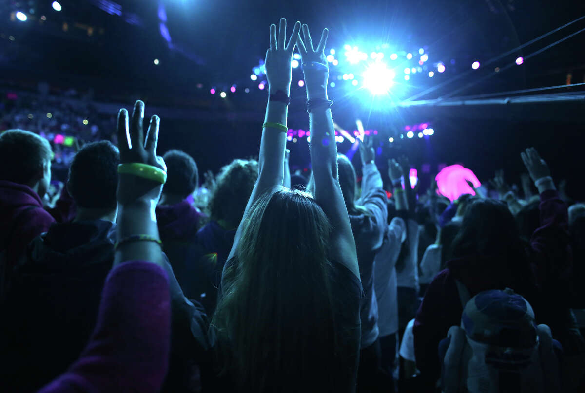 Participants raise their hands during We Day at KeyArena in Seattle. The event brought thousands of middle and high school students together to hear from a list of celebrities and motivational speakers.