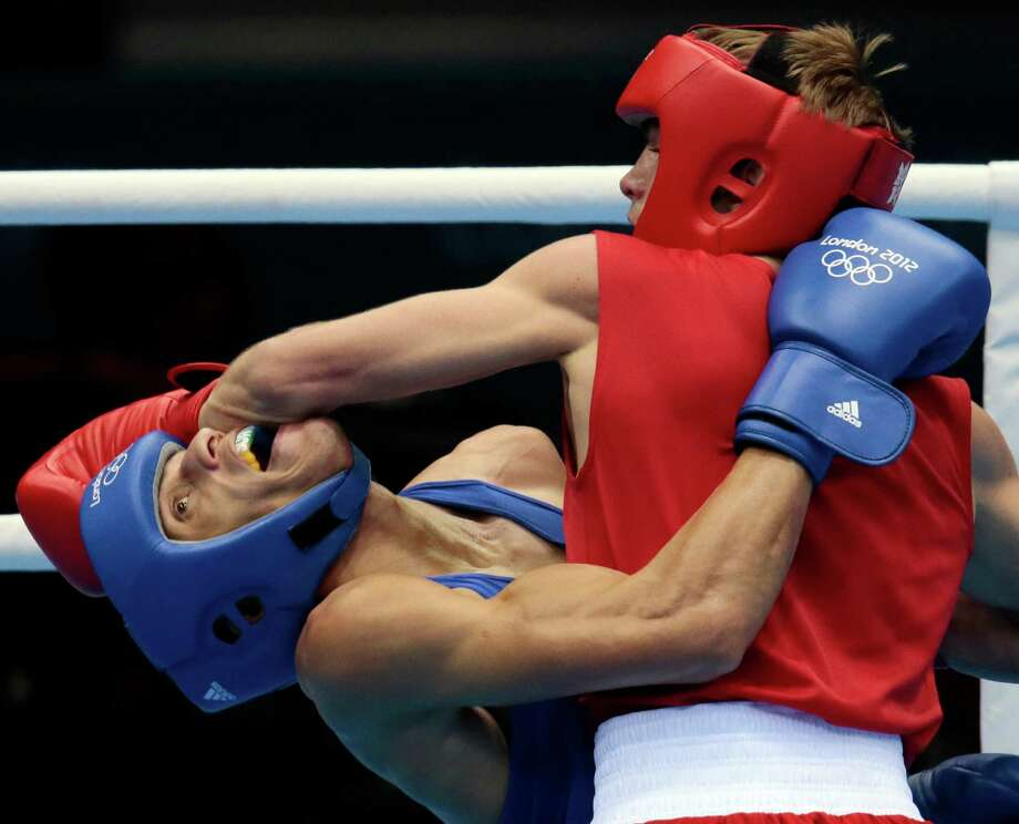 FILE - In this Aug. 1, 2012, file photo, Russia's Sergey Vodopiyanov, right, fights Brazil's Robenilson Vieira de Jesus, during their men's bantamweight 56-kilogram boxing match at the 2012 Summer Olympics in London. The International Boxing Association's plan to eliminate headgear will make for more attractive fights, and might even safely secure the Olympic future of a sport that was very iffy in the games for a while. It would also seem, at least on the surface, to be inherently more dangerous. (AP Photo/Ivan Sekretarev, File) Photo: Ivan Sekretarev