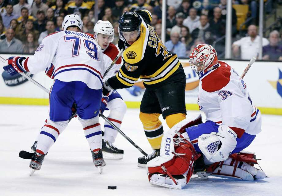 Boston Bruins' Jordan Caron (38) tries to control the puck in front of Montreal Canadiens' Carey Price (31) as Canadiens' Andrei Markov (79), of Russia, defends in the second period of an NHL hockey game in Boston, Wednesday, March 27, 2013. (AP Photo/Michael Dwyer) Photo: Michael Dwyer