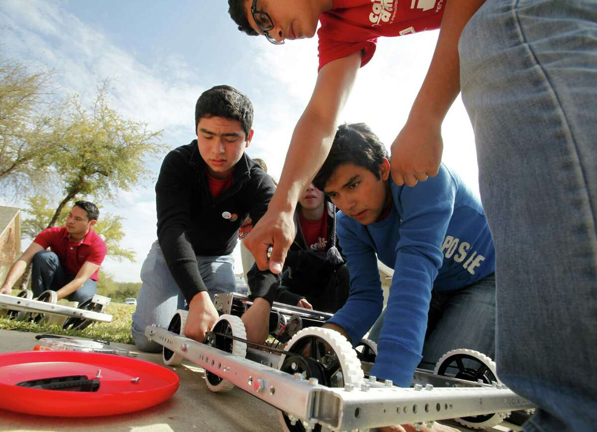 Mexican students Sergio Esteban (in black), Daniel Michel (in blue) and Jerardo Martinez (top) work to build a new robot after the truck carrying their original robot to San Antonio for the Alamo Regional FIRST Robotics competition was hijacked.