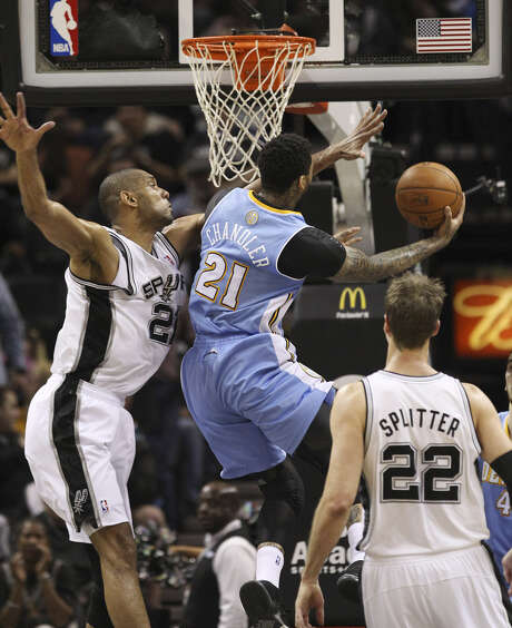 Tim Duncan attempts to block the Nuggets' Wilson Chandler during the second quarter as Tiago Splitter watches. Duncan had 23 points and five blocks. Photo: Kin Man Hui / San Antonio Express-News