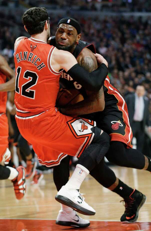 Bulls guard Kirk Hinrich (12) finds a not-so-legal way to slow down LeBron James. Photo: Nam Y. Huh, STF / AP