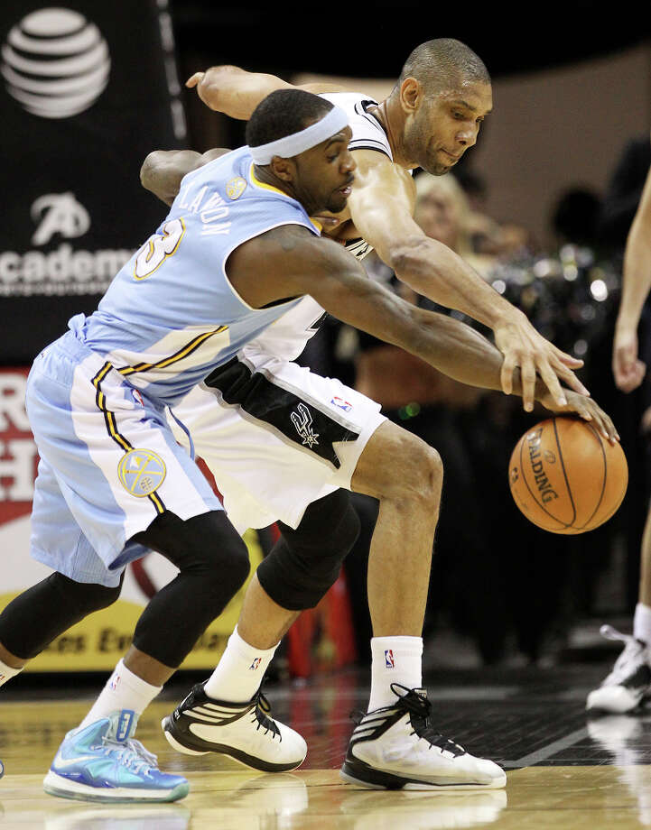 Spurs' Tim Duncan (21) competes for a loose ball against Denver Nuggets' Ty Lawson (03) in the first quarter at the AT&T Center on Wednesday, Mar. 27, 2013. Photo: Kin Man Hui, San Antonio Express-News / © 2012 San Antonio Express-News