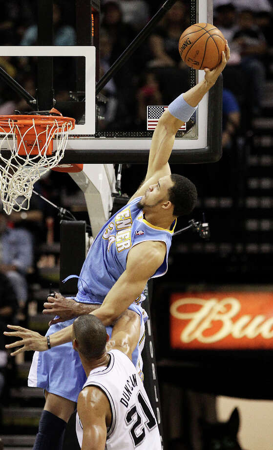 Spurs' Tim Duncan (21) looks helpless as Denver Nuggets' JaVale McGee (34) goes up for a big dunk in the first quarter at the AT&T Center on Wednesday, Mar. 27, 2013. Photo: Kin Man Hui, San Antonio Express-News / © 2012 San Antonio Express-News