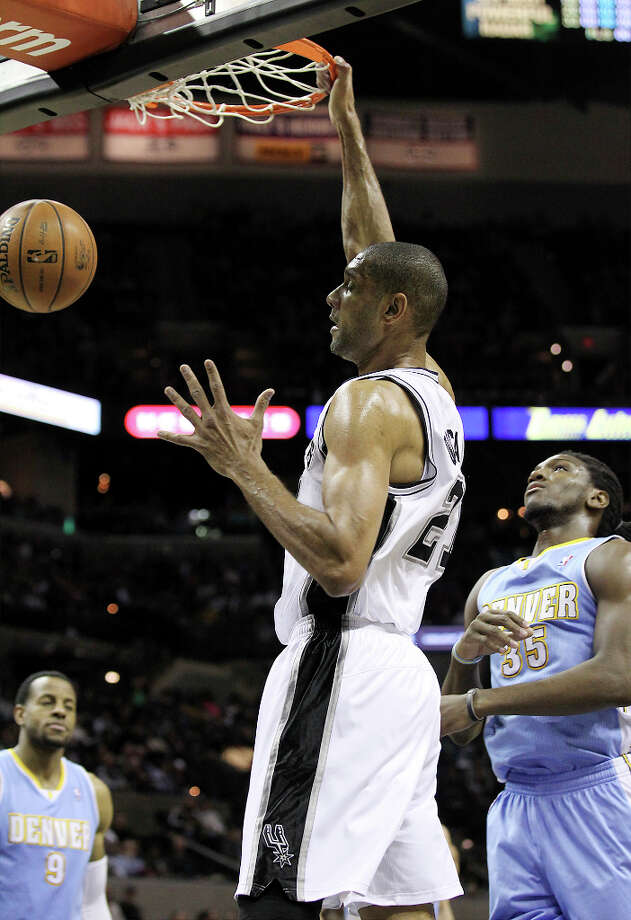 Spurs' Tim Duncan (21) dunks against Denver Nuggets' Kenneth Faried (35) in the first quarter at the AT&T Center on Wednesday, Mar. 27, 2013. Photo: Kin Man Hui, San Antonio Express-News / © 2012 San Antonio Express-News