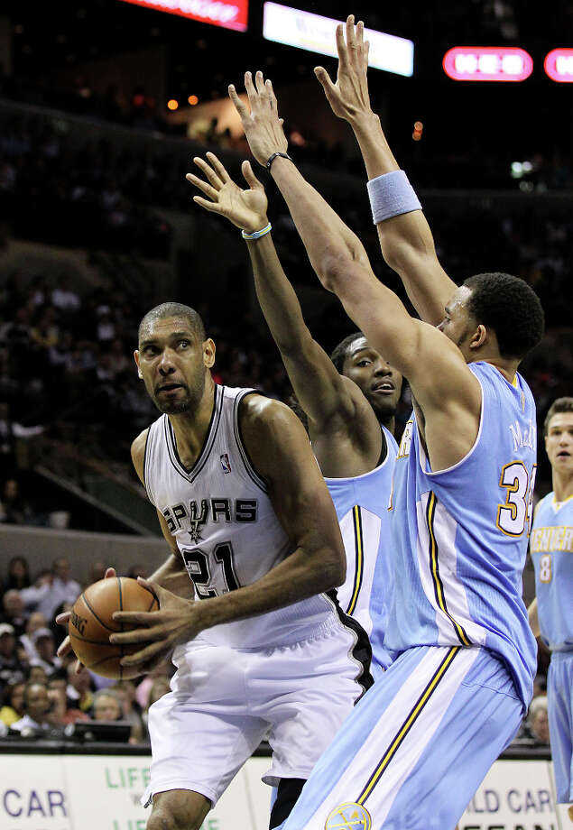 Spurs' Tim Duncan (21) gets tightly defended by Denver Nuggets' Kenneth Faried (35) and JaVale McGee (34) in the second quarter at the AT&T Center on Wednesday, Mar. 27, 2013. Photo: Kin Man Hui, San Antonio Express-News / © 2012 San Antonio Express-News