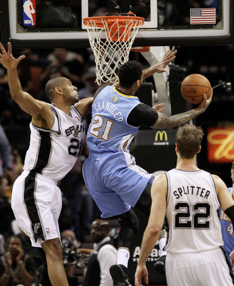 Spurs' Tim Duncan (21) attempts to defend against Denver Nuggets' Wilson Chandler (21) in the second quarter at the AT&T Center on Wednesday, Mar. 27, 2013. Photo: Kin Man Hui, San Antonio Express-News / © 2012 San Antonio Express-News