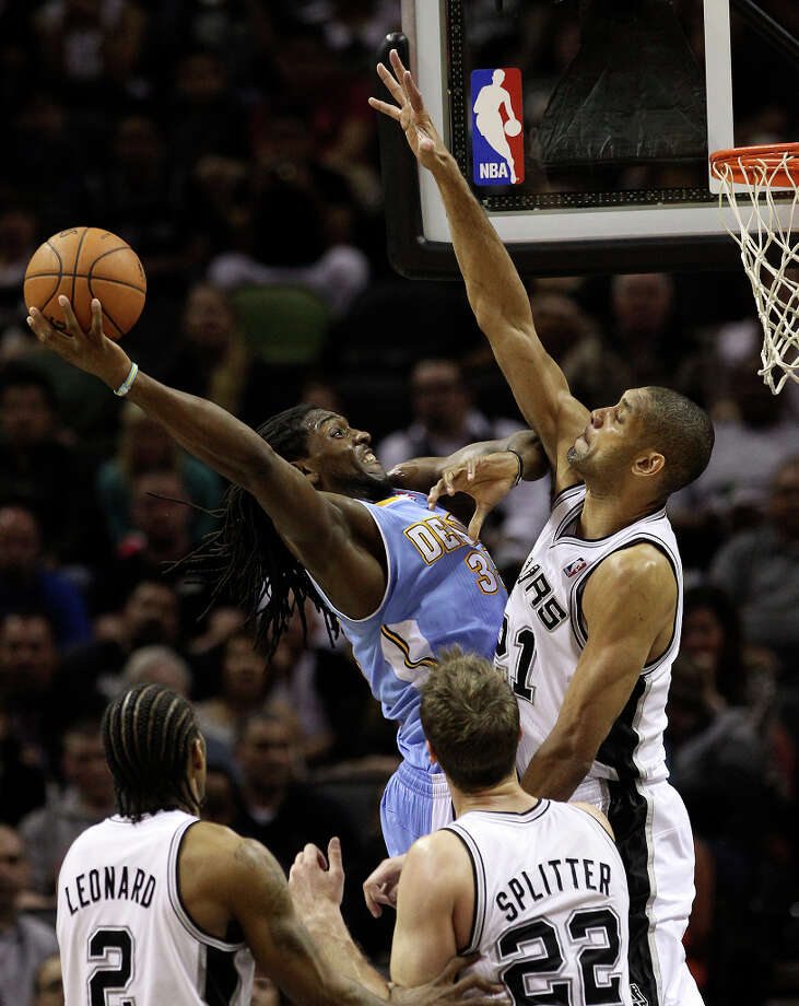 Spurs' Tim Duncan (21) defends against Denver Nuggets' Kenneth Faried (35) in the second half at the AT&T Center on Wednesday, Mar. 27, 2013. Spurs defeated the Nuggets, 100-99. Photo: Kin Man Hui, San Antonio Express-News / © 2012 San Antonio Express-News
