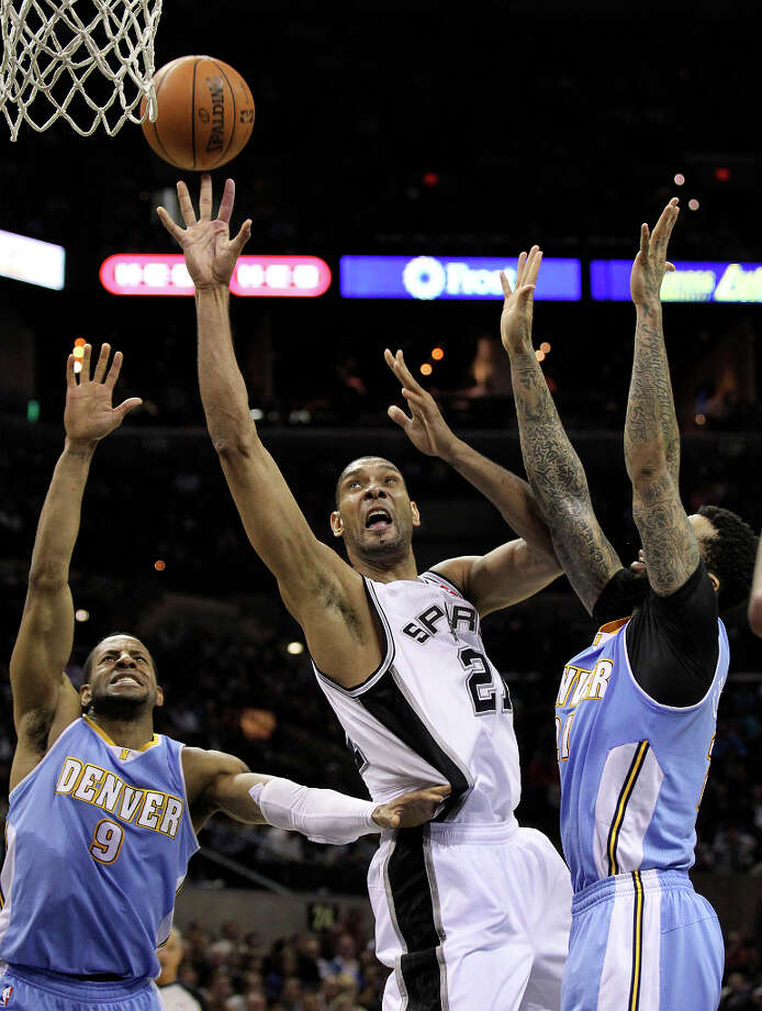 Spurs' Tim Duncan (21) goes for a shot in between Denver Nuggets' Andre Iguodala (09) and Wilson Chandler (21) in the second half at the AT&T Center on Wednesday, Mar. 27, 2013. Spurs defeated the Nuggets, 100-99. Photo: Kin Man Hui, San Antonio Express-News / © 2012 San Antonio Express-News