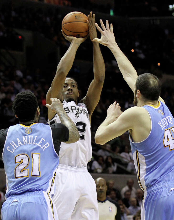 Spurs' Kawhi Leonard (02) takes a shot over Denver Nuggets' Wilson Chandler (21) and Kosta Koufos (41) in the second quarter at the AT&T Center on Wednesday, Mar. 27, 2013. Photo: Kin Man Hui, San Antonio Express-News / © 2012 San Antonio Express-News