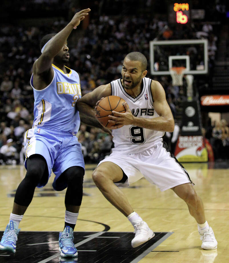 Spurs' Tony Parker (09) attempts to create some space as he drives to the basket against Denver Nuggets' Ty Lawson (03) in the second quarter at the AT&T Center on Wednesday, Mar. 27, 2013. Photo: Kin Man Hui, San Antonio Express-News / © 2012 San Antonio Express-News