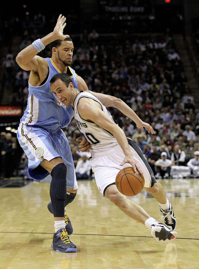 Spurs' Manu Ginobili (20) drives around against Denver Nuggets' JaVale McGee (34) in the second half at the AT&T Center on Wednesday, Mar. 27, 2013. Spurs defeated the Nuggets, 100-99. Photo: Kin Man Hui, San Antonio Express-News / © 2012 San Antonio Express-News