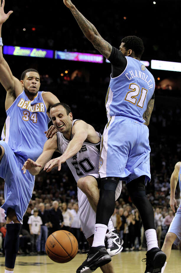 Spurs' Manu Ginobili (20) loses the ball while driving between Denver Nuggets' JaVale McGee (34) and Wilson Chandler (21) in the second half at the AT&T Center on Wednesday, Mar. 27, 2013. Spurs defeated the Nuggets, 100-99. Photo: Kin Man Hui, San Antonio Express-News / © 2012 San Antonio Express-News