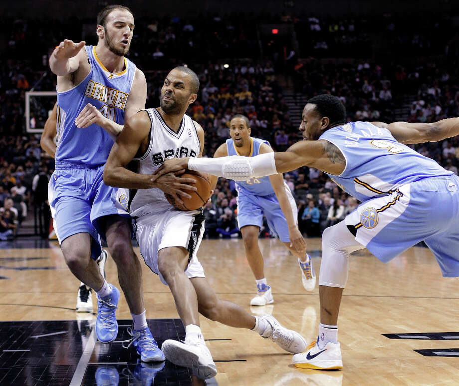 San Antonio Spurs' Tony Parker, center, of France, drives between Denver Nuggets defenders Kosta Koufos (41) and Andre Iguodala (9) during the first half of an NBA basketball game, Wednesday, March 27, 2013, in San Antonio. Photo: Eric Gay, Associated Press / AP