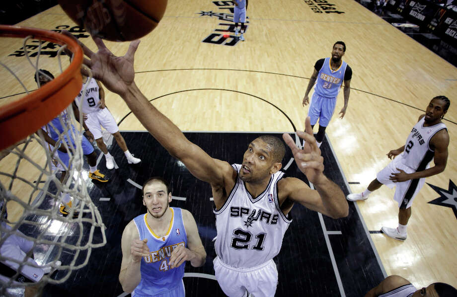 San Antonio Spurs' Tim Duncan (21) grabs a rebound over Denver Nuggets' Kosta Koufos (41) during the first half of an NBA basketball game, Wednesday, March 27, 2013, in San Antonio. Photo: Eric Gay, Associated Press / AP