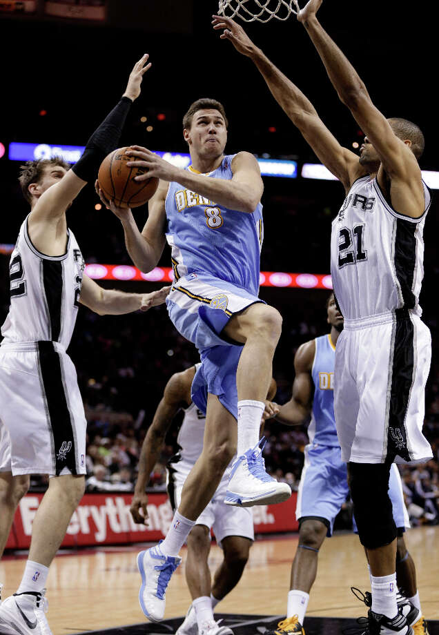 Denver Nuggets' Danilo Gallinari (8) drives to the basket between San Antonio Spurs'  Tiago Splitter, left, of Brazil, and Tim Duncan (21) during the second half of an NBA basketball game, Wednesday, March 27, 2013, in San Antonio. San Antonio won 100-99. Photo: Eric Gay, Associated Press / AP
