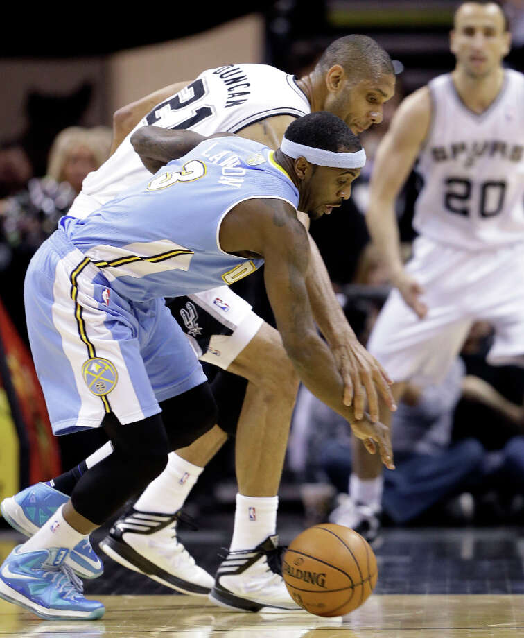San Antonio Spurs' Tim Duncan (21) and Denver Nuggets' Ty Lawson (3) chase a loose ball during the first half of an NBA basketball game, Wednesday, March 27, 2013, in San Antonio. Photo: Eric Gay, Associated Press / AP