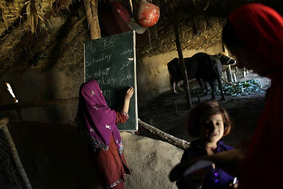 A Pakistani schoolgirl, center, writes on the blackboard while her teacher, Warda Arshad, 20, right, checks the homework of another student in a makeshift school set in a clay house, partially used as a cowshed, in a poor neighborhood on the outskirts of Islamabad, Pakistan, Wednesday, March 27, 2013. Threats from militant groups is one of many obstacles Pakistani girls and teachers face in getting and providing an education. Others include rampant poverty, harassment and the government's failure to prioritize education spending. Both sexes have suffered from the lack of funding, but girls, who have lower rates of literacy and school attendance, are in a particularly perilous position. (AP Photo/Muhammed Muheisen) Photo: Muhammed Muheisen, Associated Press