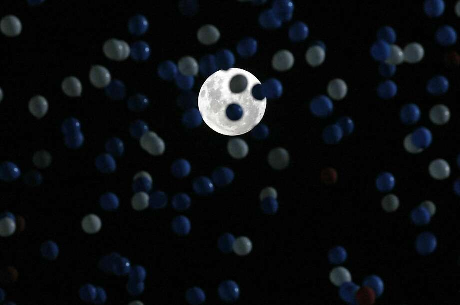 Backdropped by a full moon, thousands of balloons are released into the night sky honoring the Chilean soccer team at their 2014 World Cup qualifying soccer match against Uruguay in Santiago, Chile,  Tuesday, March 26, 2013. (AP Photo/Luis Hidalgo) Photo: Luis Hidalgo, Associated Press