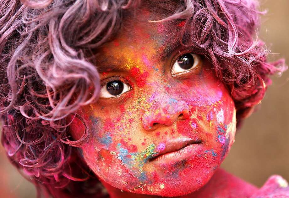 An Indian child, face smeared with colored powder, celebrates Holi festival in Mumbai, India, Wednesday, March. 27, 2013. Holi, the Hindu festival of colors that also marks the advent of spring, is being celebrated across the country Wednesday.(AP Photo/Rajanish Kakade) Photo: Rajanish Kakade, Associated Press