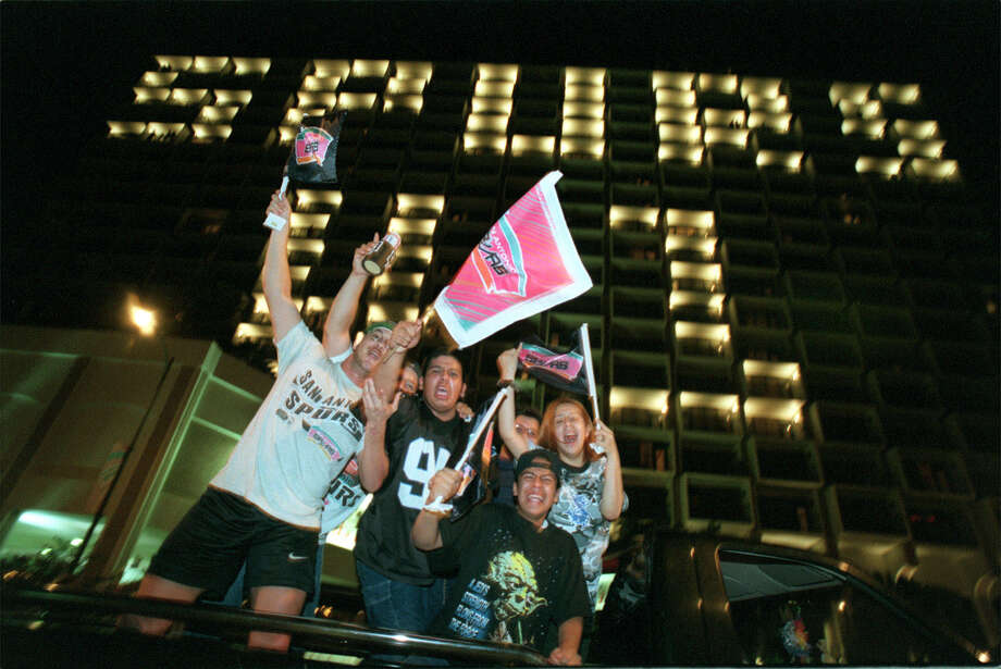 Spurs fans cheer as they pass the Hilton Palacio del Rio Hotel downtown after the Spurs beat the New York Knicks on June 25, 1999, in Game 5 to win the NBA Championship.