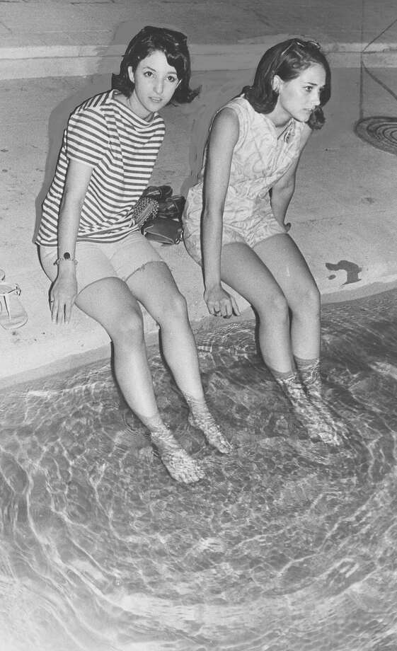 Kaye Nader and Brenda Herbert soak their feet in a fountain after walking down the tower stairs after a power failure on May 22, 1968. Photo: San Antonio Express-News File Photo