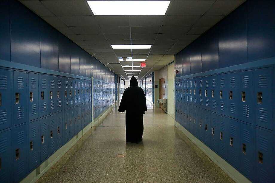 "Virginia Beach Police Department officer, John Vanderheiden II, dressed as ""Grim Reaper,"" walks the hallway to summon killed students who participate in the ""Every 15 Minutes"" program Wednesday, March 27, 2013, at the First Colonial High School in Virginia Beach, Va. ""Every 15 Minutes"" is a two-day role-playing interactive program involving junior and senior high school students and their parents. Students learn the results of their decisions in dealing with teenage drinking, personal safety, and making mature decisions when lives are involved. (AP Photo/The Virginian-Pilot, Hyunsoo Leo Kim)  MAGS OUT Photo: Hyunsoo Leo Kim, Associated Press"