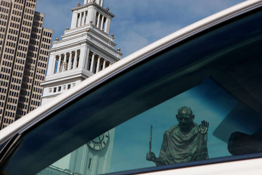 The Gandhi statue is seen through a parked car. His staff has been broken since late 2012 and his glasses missing since at least February. Photo: Liz Hafalia, The Chronicle / SFC