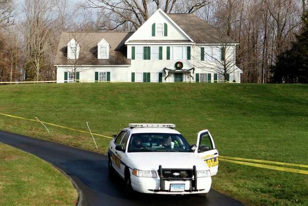A police cruiser sits in the driveway as crime scene tape surrounds the home of Nan