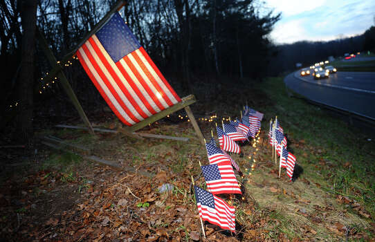 Homeowner Paul Sullivan set up 27 little US flags and lights around a larger flag in memory of the victims from yesterday's mass shooting at Sandy Hook Elementary School, at the edge of his property along I84 in Newtown, Conn. on Saturday December 2012. The larger flag was put up back on 9/11 and was replaced every other year or so. Sullivan thought it would be fitting to add the little flags because of the tragedy. Photo: Christian Abraham / Connecticut Post